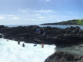 Surveyors count and size 'opihi makaiauli from the water while others record data and watch for waves