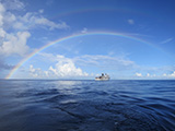 The NOAA Ship Hi'ialakai somewhere under the rainbow at Rose Atoll Marine National Monument, American Samoa.  Credit: NOAA