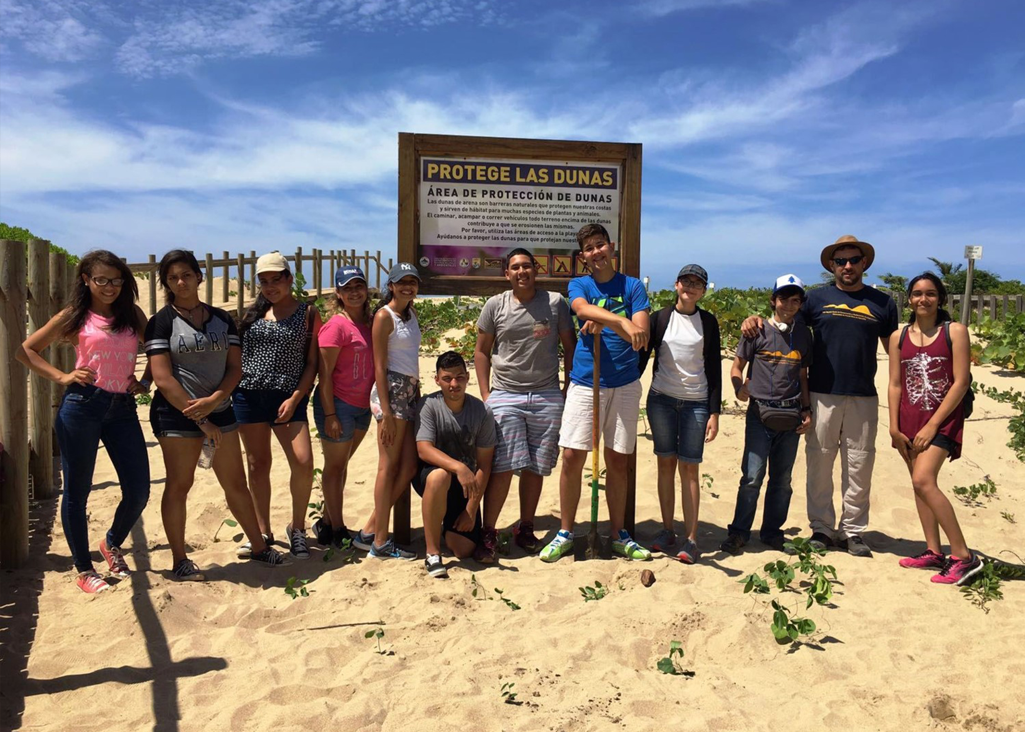 Volunteers at sign to educate beach users of importance of dune restoration projects to protect dune ecosystems in Puerto Rico.