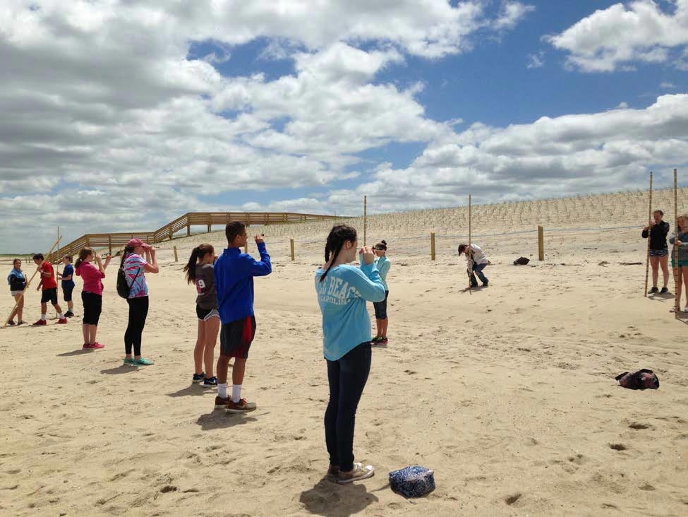 Middle school students use measuring poles and levels outside on a beach