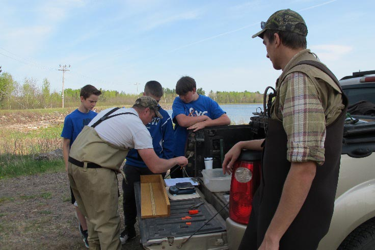 Students help Dumke set up his scales to weigh fish.