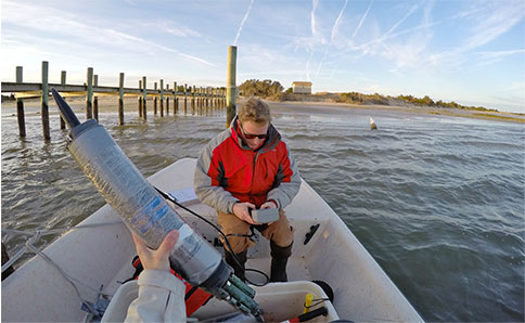 Photo of a person in a boat looking at a data logger