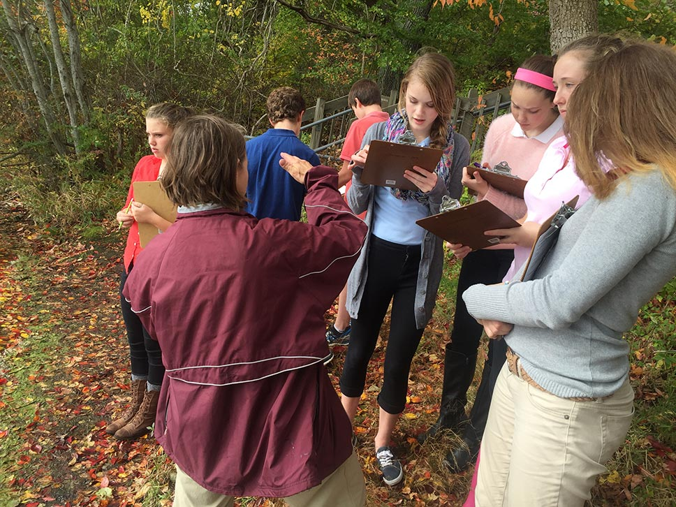 Students and teacher discussing stewardship project  ideas outdoors