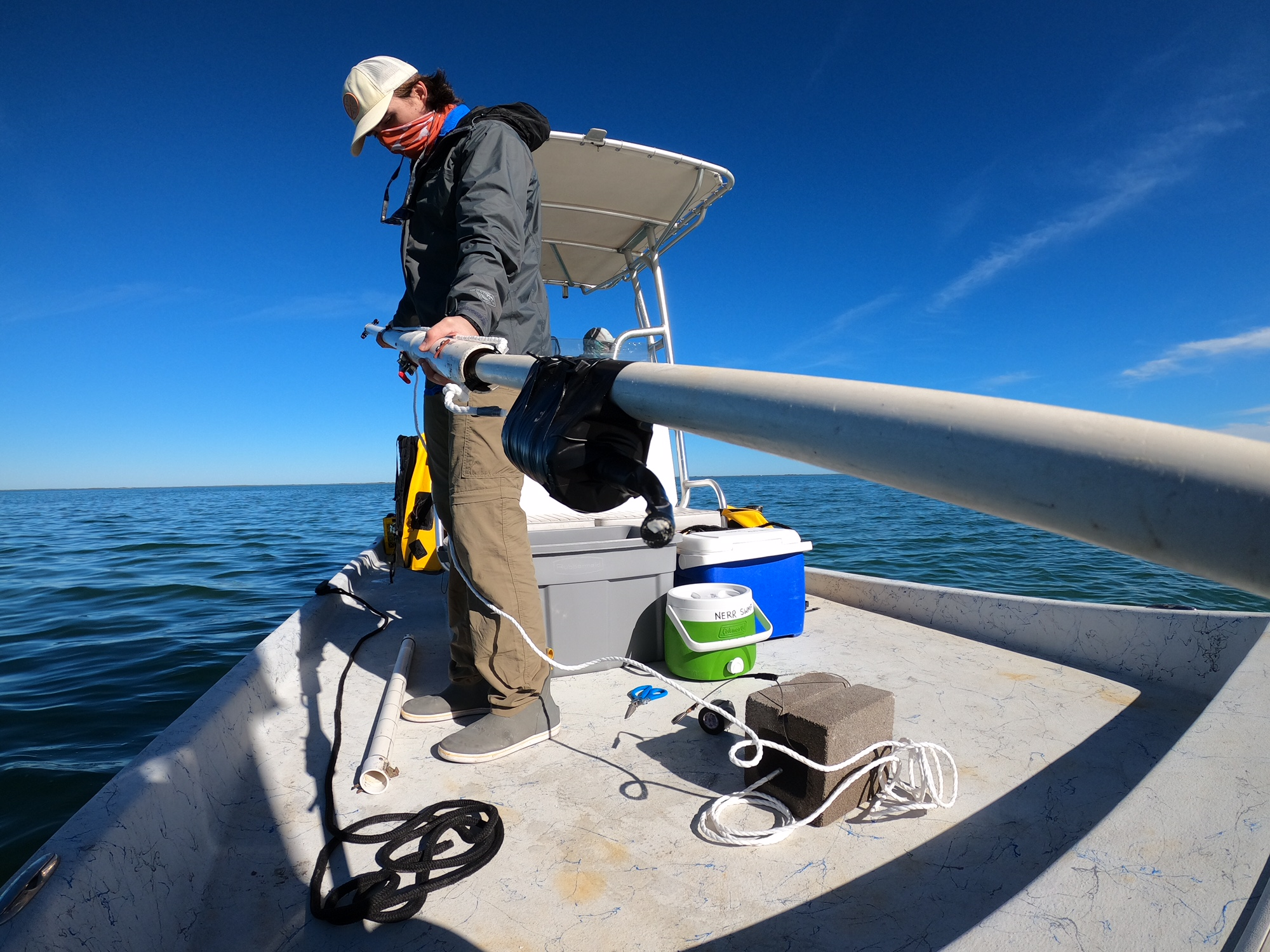 Fellow assembling equipment on a boat in the ocean.