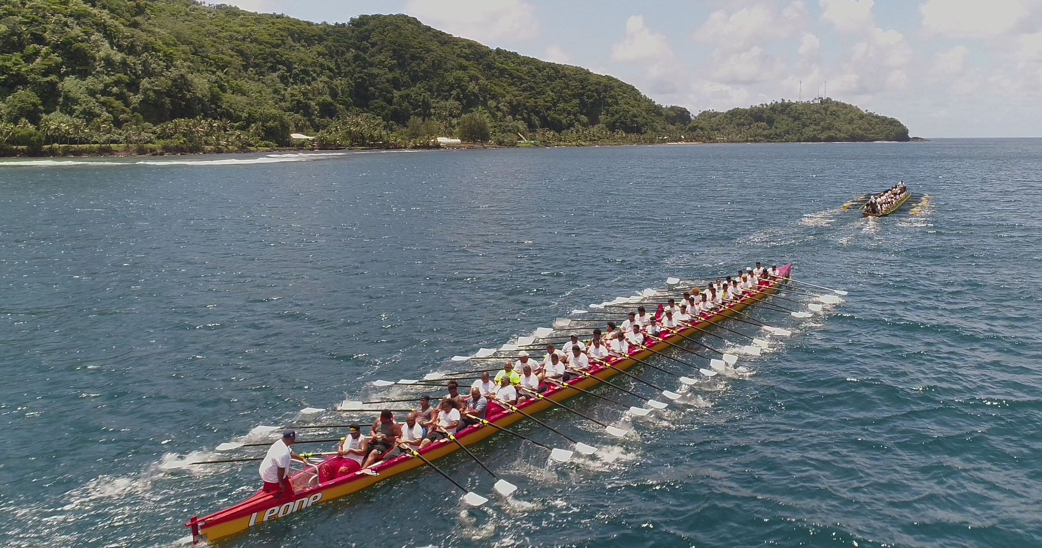 Traditional canoes race on the ocean near land in American Samoa. Each boat has about 40 paddlers.