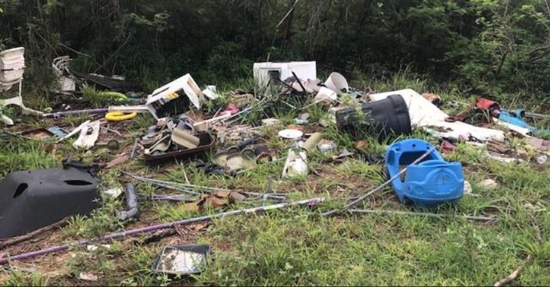 Large pieces of coastal and marine debris lie in the grass near a beach in Saipan.