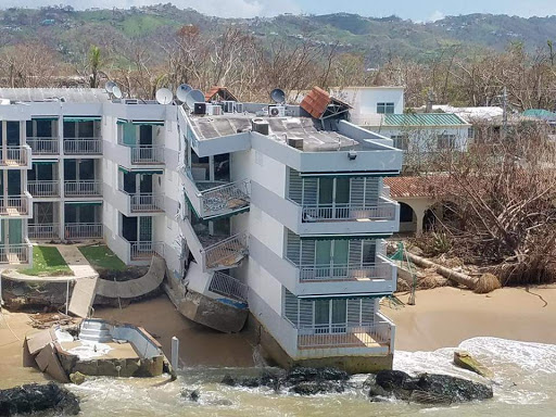 Building off a beach in Puerto Rico showing significant structural damage as a likely result of storms. Damage to nearby trees is also visible.